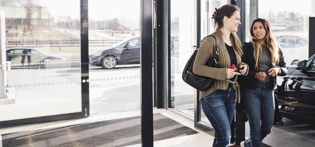 Mujeres hablando sobre las opciones de refinanciación de automóviles