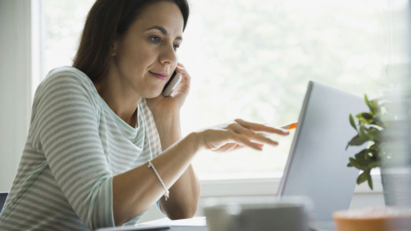 A woman at a computer on the phone listening to her financial advisor